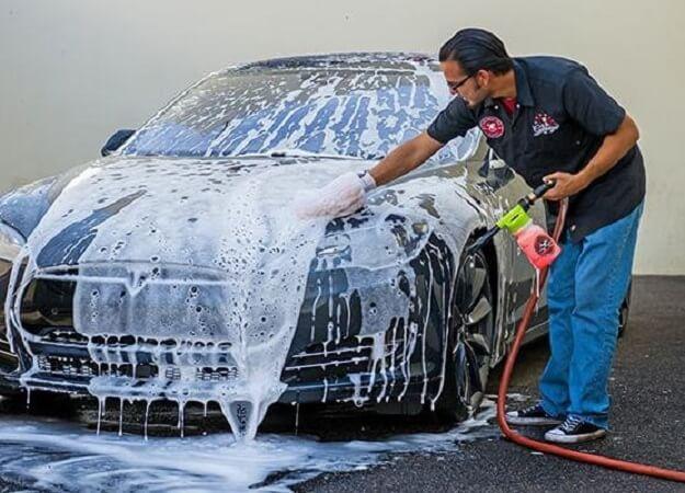 Thực hiện phun dung dịch rửa xe lên bề mặt xe ô tô